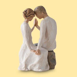 figurine with a couple touching hands